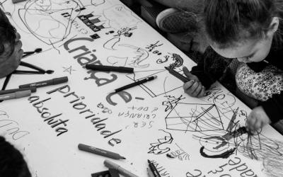 """Foto em preto e branco criança escrevendo em cartaz apoiado no chão. No cartaz, o texto: """"criança é prioridade absoluta"""""""