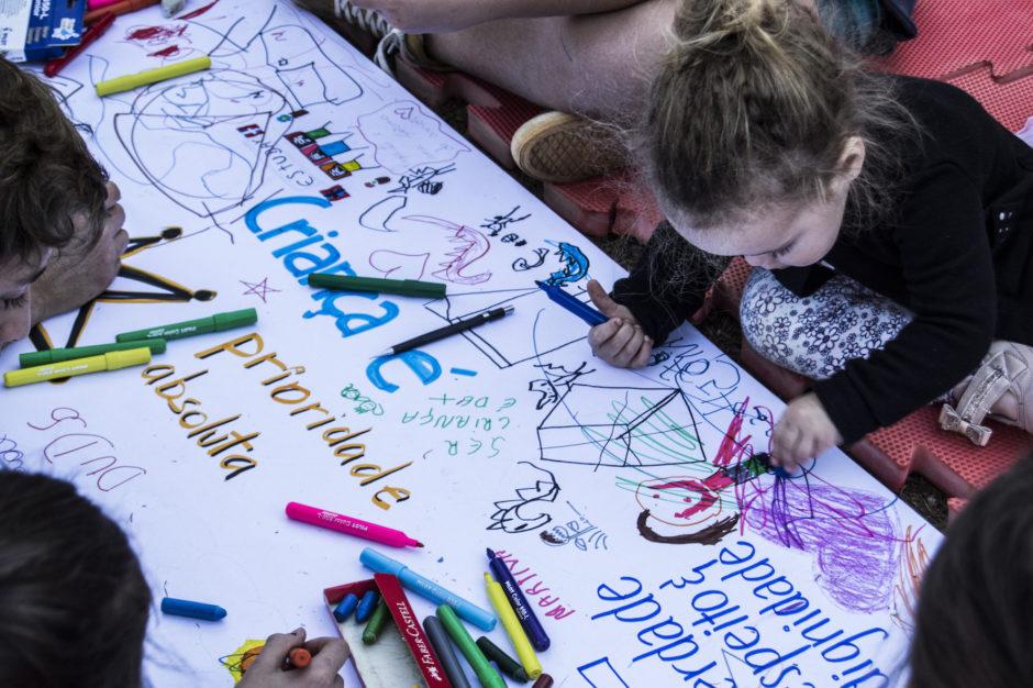 Uma foto com perspectiva superior, mostrando uma menina desenhando.