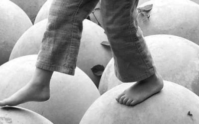 Foto em preto e branco de pés de criança, andando sobre bolas.