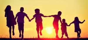 Foto com silhuetas de crianças de costas, com as mãos dadas elas correm em direção ao pôr do sol.