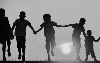 Foto em preto e branco, contraluz, de crianças correndo com as mãos dadas