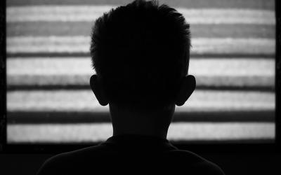 Foto em preto e branco de de criança de costas assistindo uma TV que está fora do ar