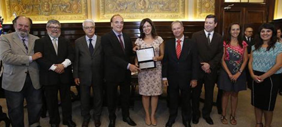 Foto composta por várias pessoas, um homem e uma mulher estão segurando um prêmio em mãos.