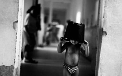 Foto em preto e branco de criança com balde na cabeça