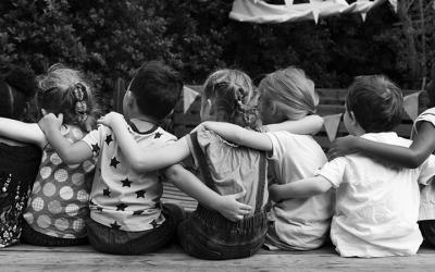 Foto em preto e branco de crianças de costas abraçadas