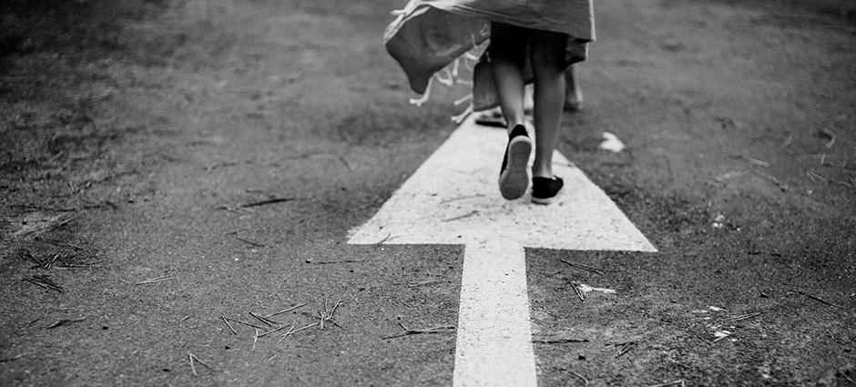 Foto preto e branca de uma pessoa caminhando em uma rua, em cima de uma seta desenhada no chão.