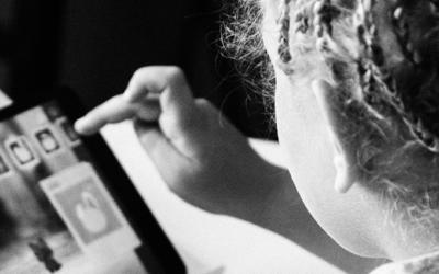 Foto preto e branco de uma garota de costas mexendo em um tablet.