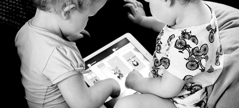 Foto preto e branco com dois bebês mexendo em um tablet.