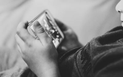 Foto preto e branca de uma criança interagindo com um celular.