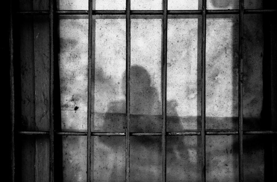 Foto de uma jaula de prisão com uma sombra da silhueta de duas pessoas.