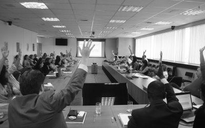 Foto de Assembleia Ordinária do Conanda. Pessoas sentadas em mesa com as mãos levantadas durante votação