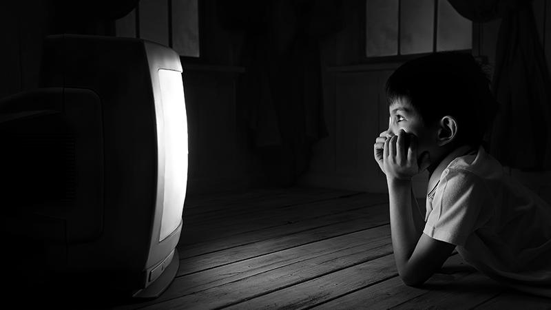Foto em preto e branco de criança assistindo TV