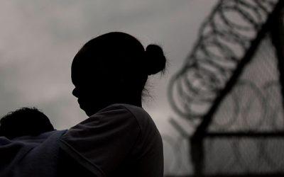 Foto contraluz de mulher segurando criança, ao fundo, grades