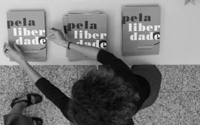 Foto em preto e branco, de ângulo superior, de mulher arrumando os livros 'Pela Liberdade' em mesa