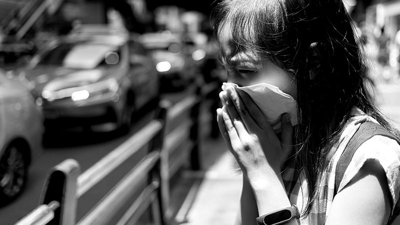 Foto em preto e branco de criança com lenço de papel no nariz como se espirasse. Ao fundo, vários carros.