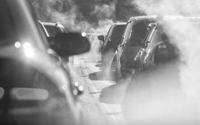 Foto de vários carros em trânsito envoltos pela fumaça dos escapamentos