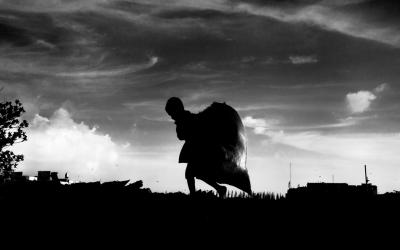 Foto em preto e branco de criança carregando saco