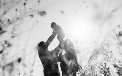 Foto em preto e branco, contraluz, de casal brincando com criança