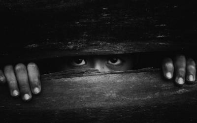Foto em preto e branco de criança olhando por fresta de táboa