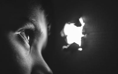 Foto em preto e branco de criança espiando por fresta