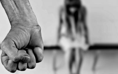 Foto em preto e branco de, em primeiro plano, um punho serrado e, ao fundo, criança com a cabeça baixa