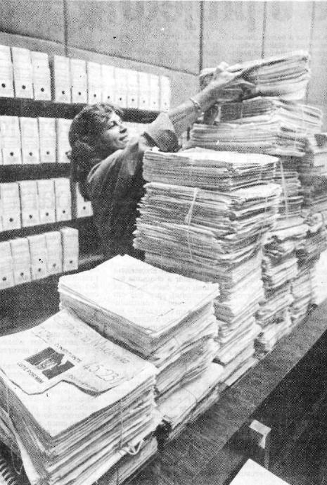 Foto em preto e branco do registro da chegada das várias pilhas de papel, com as assinaturas para a emenda popular 'Criança, prioridade nacional', no Congresso brasileiro. Uma mulher está empilhando os papeis.
