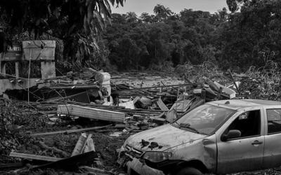 Foto em preto e branco de casas, carros e árvores destruídos pela lama em Brumadinho