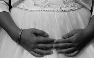 Foto em preto e branco de menina com vestido de noiva e as mãos estendidas sobre o colo