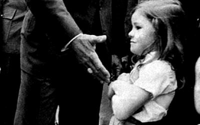 Foto em preto e branco de João Figueiredo, à época (1979) presidente do Brasil, com a mão estendida para cumprimentar criança que se recusa, com os braços cruzados.