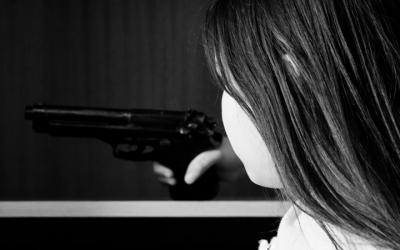 Foto em preto e branco de criança segurando arma dentro de guarda-roupa