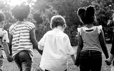 Foto em preto e branco de crianças de costas com as mãos dadas.