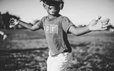 foto em preto e branco de criança sorrindo com os braços abertos