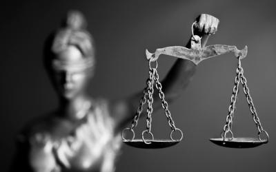Foto em preto e branco de estatua da justiça segurando balança