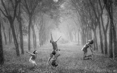 Foto em preto e branco de 4 crianças pulando para alcançar uma bola