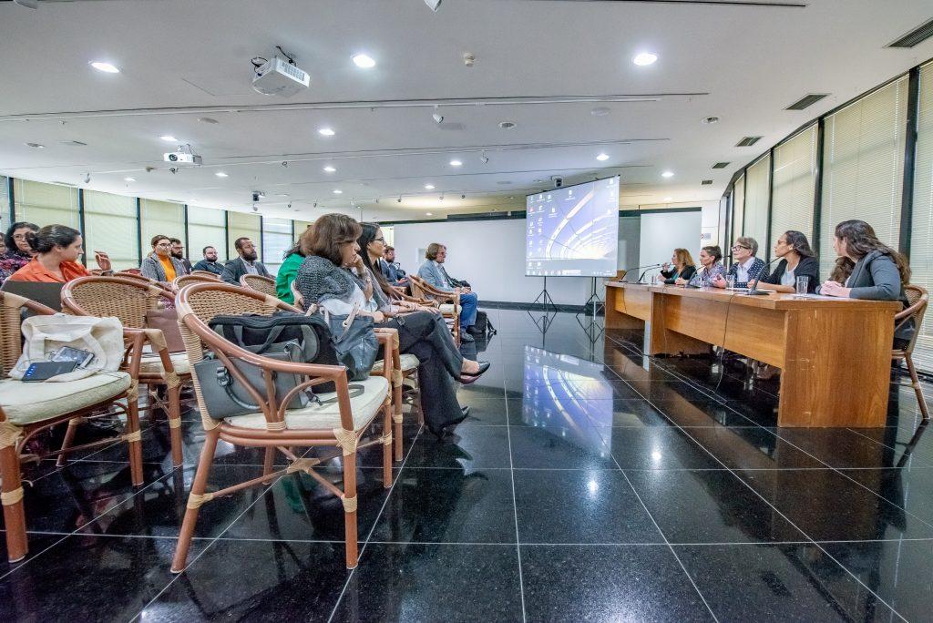 Foto do evento mostra palestrantes sentadas à mesa e público sentado em cadeiras assistindo