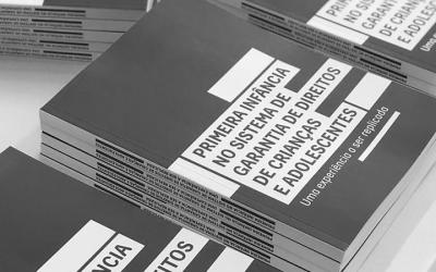 Foto mostra pilha de livros 'A primeira infância no sistema de garantia de direitos de crianças e adolescentes'