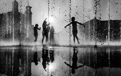 Foto em preto e branco de crianças brincando em água