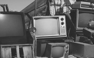 Foto em preto e branco de amontoado de tvs antigas