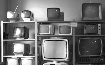 Foto em preto e branco de prateleira com várias televisões antigas