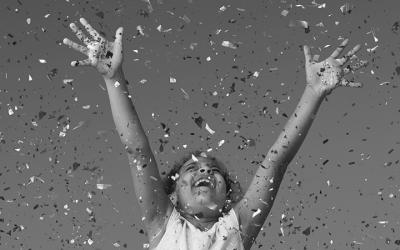 Foto em preto e branco de criança com as mãos erguidas comemorando enquanto uma chuva de confetes cai sobre ela.