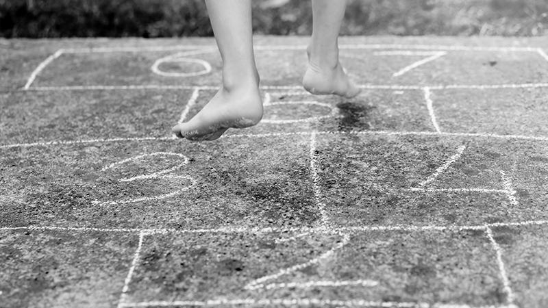 Foto em preto e branco de pés de criança pulando em amarelinha desenhada com giz no chão