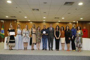 Foto do evento de premiação das iniciativas, no TJDFT, mostra pessoas em pé em frente à mesa
