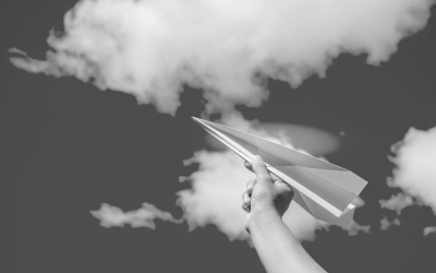 Foto em preto e branco de criança segurando aviãozinho de papel