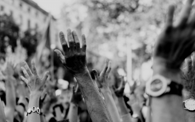 Foto em preto e branco de várias mãos levantadas