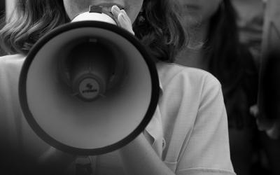 Foto em preto e branco de criança segurando um megafone