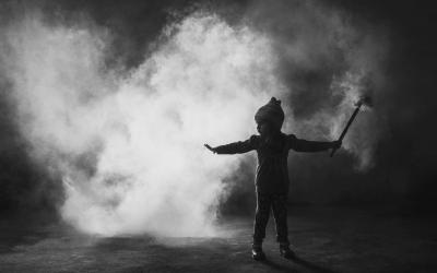 Foto em preto e branco de criança segurando fogos, ao fundo, muita fumaça - mudanças climáticas