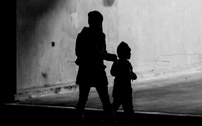 Foto contraluz em preto e branco de duas crianças caminhando de mãos dadas