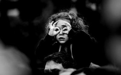 Foto em preto e branco de criança fazendo um óculos com os dedos em volta dos olhos.