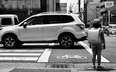 Foto em preto e branco de criança parada em faixa de pedestre enquanto carros passam - expresso poluição do ar