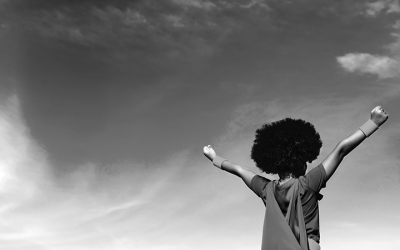 Foto em preto e branco de criança negra de costas, com os braços levantados celebrando.